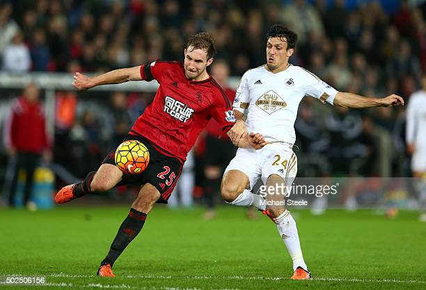 Craig Dawson of West Bromwich Albion clears the ball under pressure from Jack Cork of Swansea City during the Barclays Premier League match between...