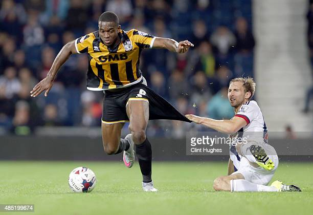 Craig Dawson of West Bromwich Albion fouls Uche Ikpeazu of Port Vale during the Capital One Cup Second Round match between West Bromwich Albion and...