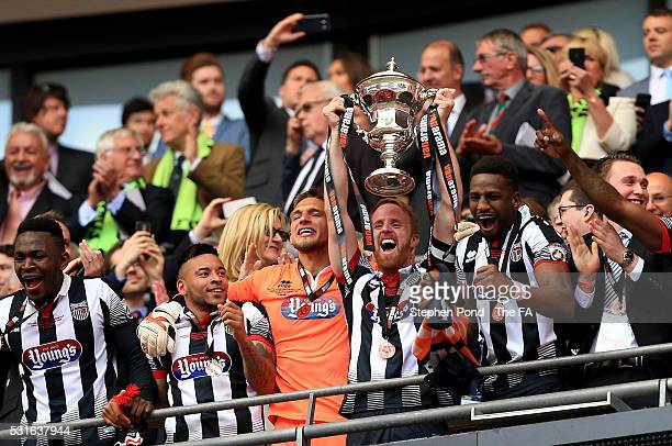 Craig Disley of Grimsby Town lifts the trophy with team mates during the Vanarama Football Conference League Play Off Final match between Forest...