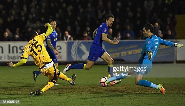 Craig Eastmond of Sutton United shoots while James Shea of AFC Wimbledon saves during the Emirates FA Cup third round replay between AFC Wimbledon...