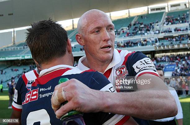 Craig Fitzgibbon of the Roosters embraces a team mate after the round 26 NRL match between the Sydney Roosters and the North Queensland Cowboys at...