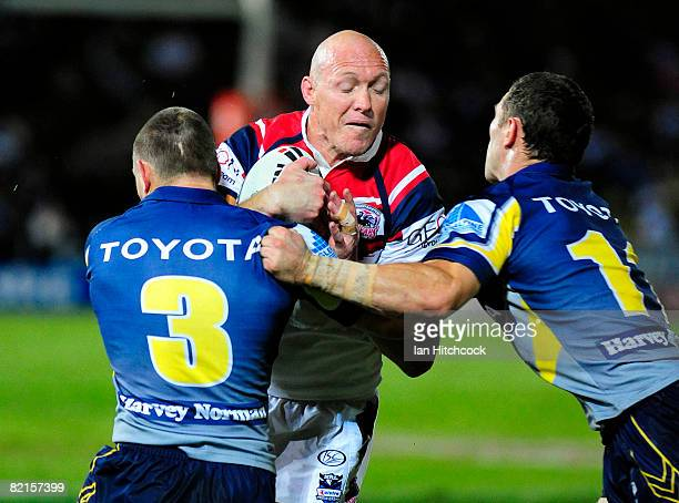 Craig Fitzgibbon of the Roosters is tackled by Mark Henry and Luke O'Donnell of the Cowboys during the round 21 NRL match between the North...