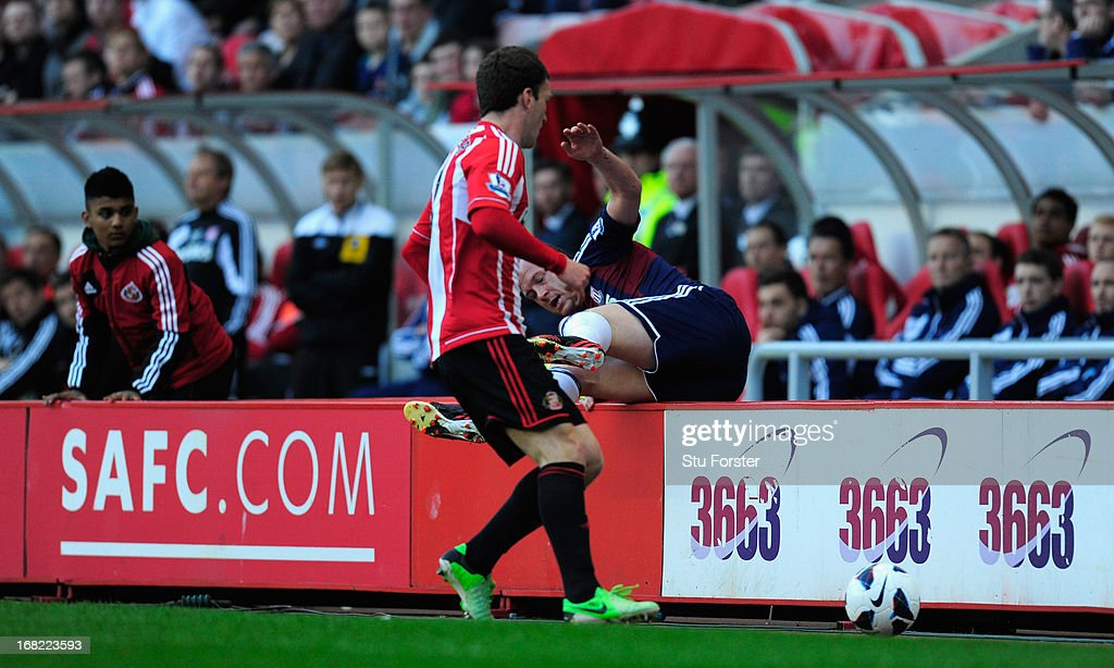 Craig Gardner of Sunderland looks on as <a gi-track='captionPersonalityLinkClicked' href=/galleries/search?phrase=Charlie+Adam&family=editorial&specificpeople=3987843 ng-click='$event.stopPropagation()'>Charlie Adam</a> of Stoke takes a tumble of the Ad boards during the Barclays Premier League match between Sunderland and Stoke City at the Stadium of Light on May 06, 2013 in Sunderland, England.