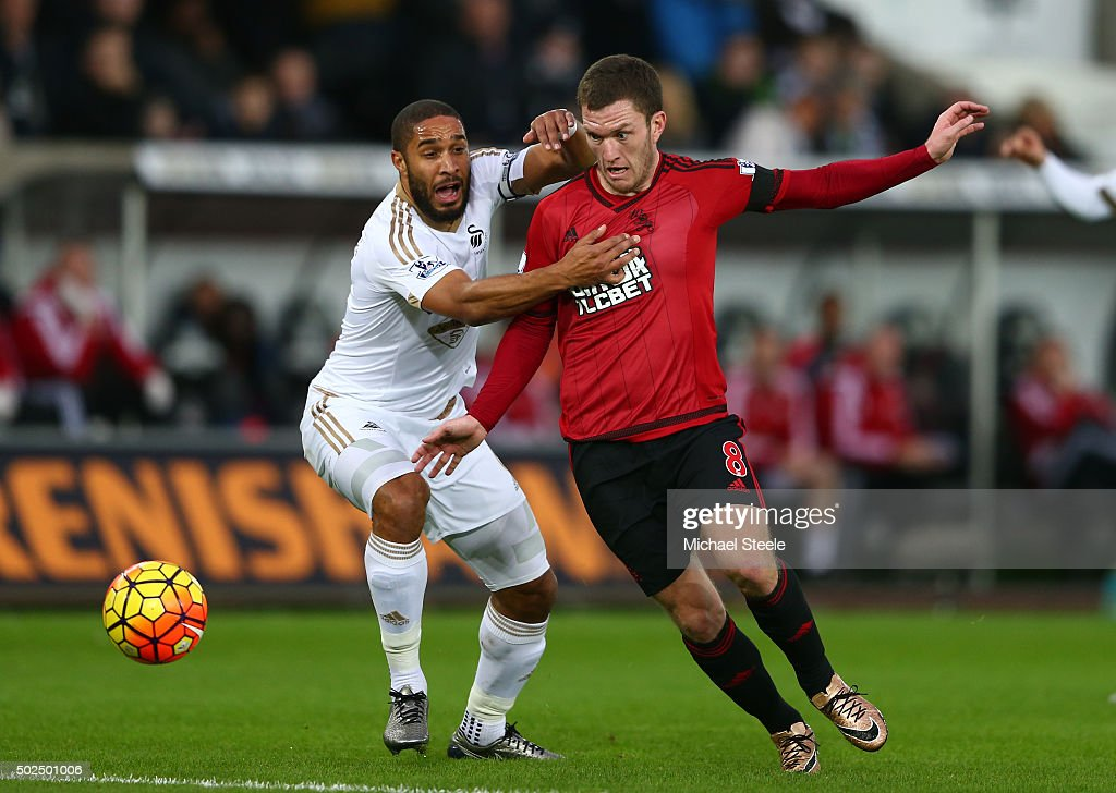 Craig Gardner of West Bromwich Albion is challenged by Ashley Williams of Swansea City during the Barclays Premier League match between Swansea City and West Bromwich Albion at the Liberty Stadium on December 26, 2015 in Swansea, Wales.