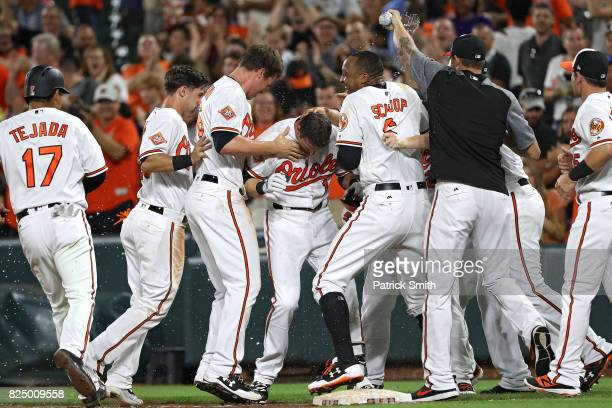 Craig Gentry of the Baltimore Orioles celebrates with teammates after hitting a walkoff RBI single during the ninth inning against the Kansas City...