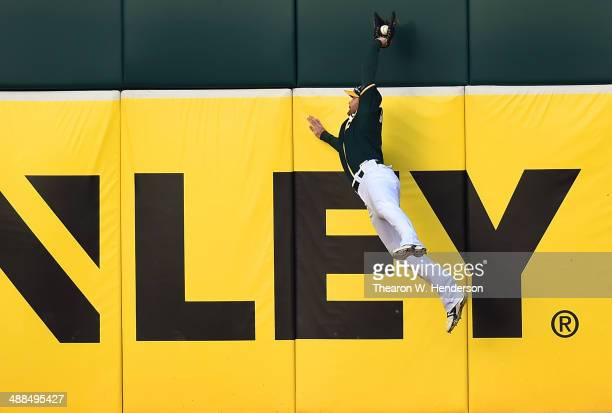 Craig Gentry of the Oakland Athletics leaps at the wall to take a hit away from Corey Hart of the Seattle Mariners in the top of the first inning at...