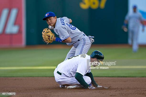 Craig Gentry of the Oakland Athletics slides into second base to break up a double play attempt by Munenori Kawasaki of the Toronto Blue Jays during...