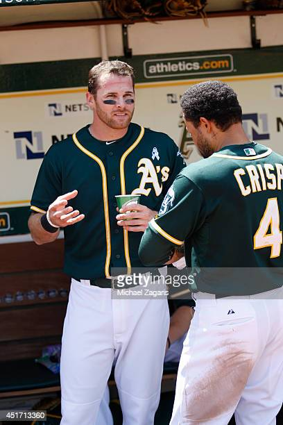 Craig Gentry of the Oakland Athletics talks with Coco Crisp during the game against the New York Yankees at Oco Coliseum on June 15 2014 in Oakland...