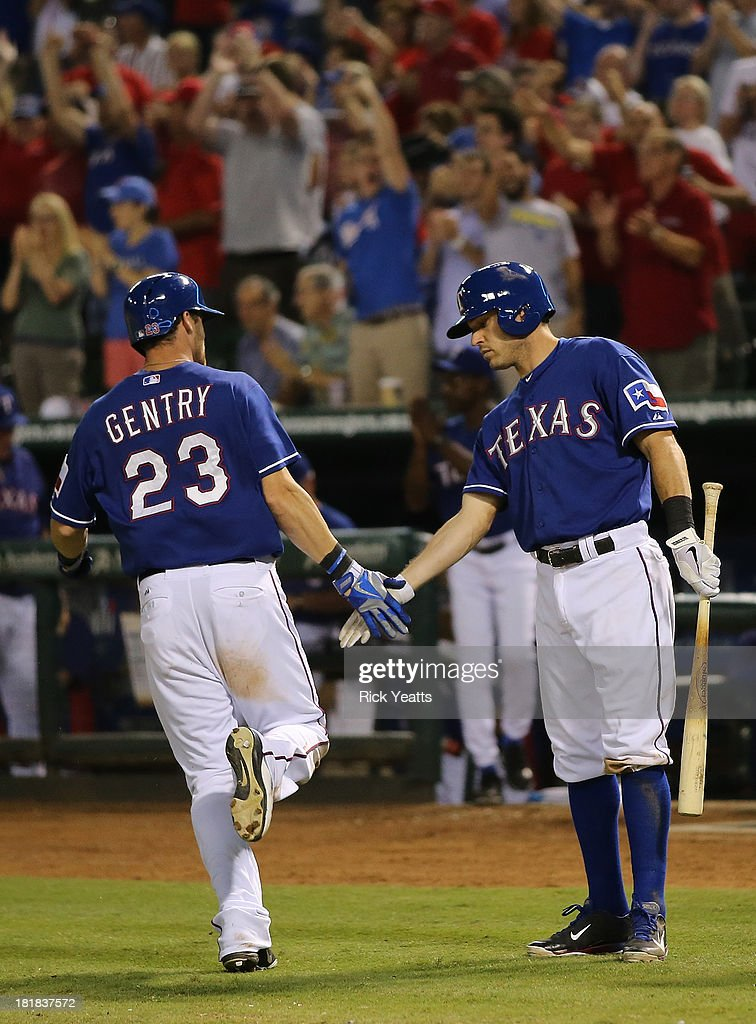 <a gi-track='captionPersonalityLinkClicked' href=/galleries/search?phrase=Craig+Gentry&family=editorial&specificpeople=6352553 ng-click='$event.stopPropagation()'>Craig Gentry</a> #23 of the Texas Rangers is congratulated by <a gi-track='captionPersonalityLinkClicked' href=/galleries/search?phrase=Ian+Kinsler&family=editorial&specificpeople=538104 ng-click='$event.stopPropagation()'>Ian Kinsler</a> #5 for scoring in the third inning against the Houston Astros at Rangers Ballpark in Arlington on September 25, 2013 in Arlington, Texas.
