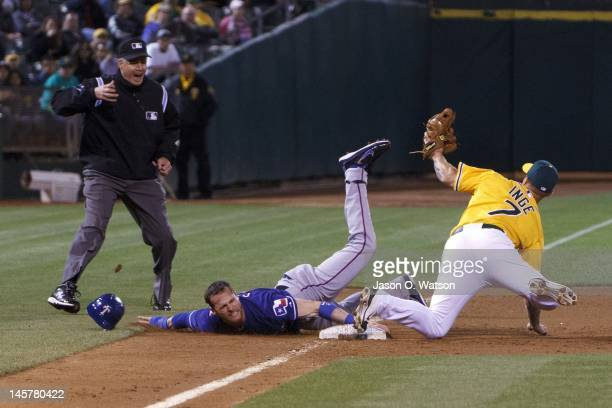 Craig Gentry of the Texas Rangers is tagged out by Brandon Inge of the Oakland Athletics attempting to steal third base in front of umpire Gary...