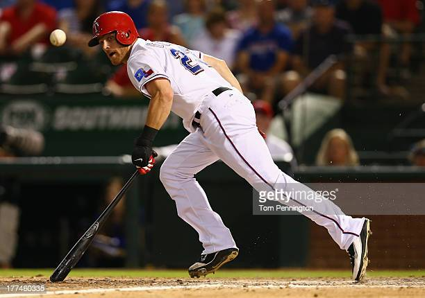 Craig Gentry of the Texas Rangers lays down a bunt against the Houston Astros at Rangers Ballpark in Arlington on August 21 2013 in Arlington Texas