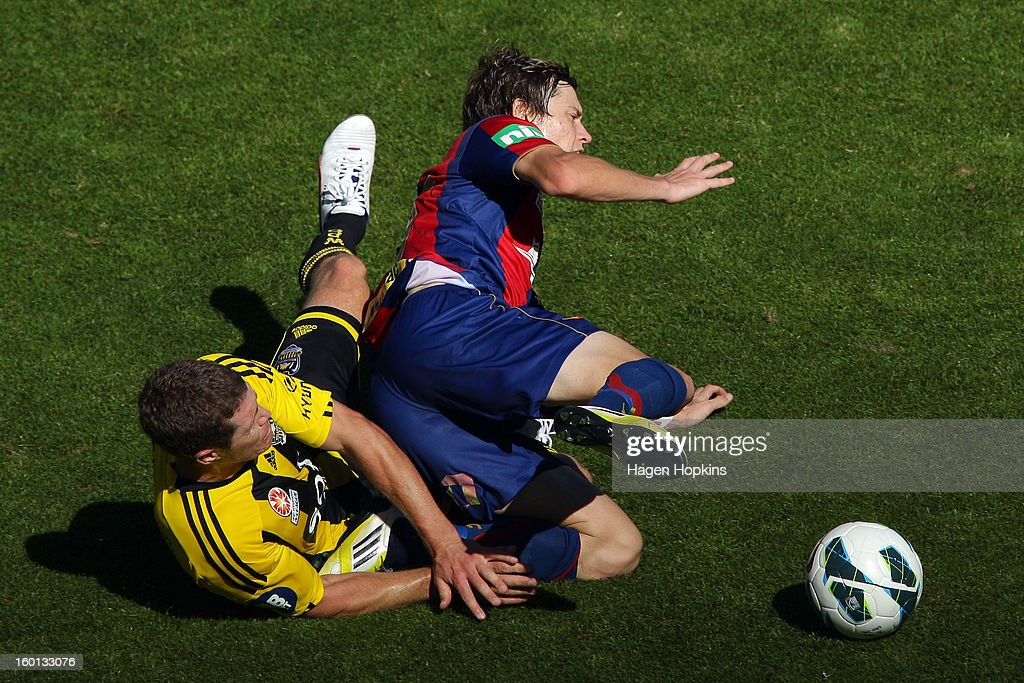Craig Goodwin of the Jets goes to ground in the tackle of Tony Lochhead of the Phoenix during the round 18 A-League match between the Wellington Phoenix and the Newcastle Jets at Westpac Stadium on January 27, 2013 in Wellington, New Zealand.