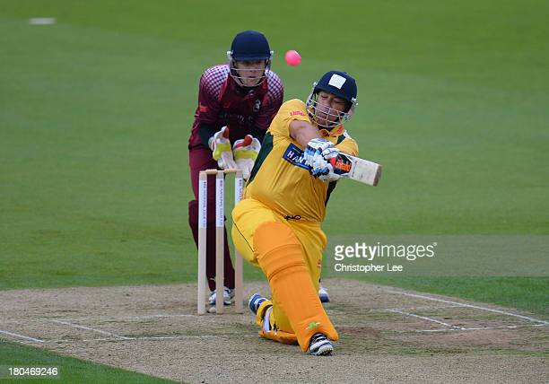 Craig Haupt of Banbury smashes the ball for a six as wicket keeper James Brown of Wimbledon watches during the Semi Final match between Wimbledon and...