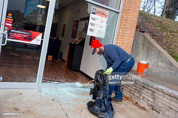 Craig Kidd helps to clean up after violent protests damaged businesses following the grand jury announcement in the Michael Brown case on November 25...