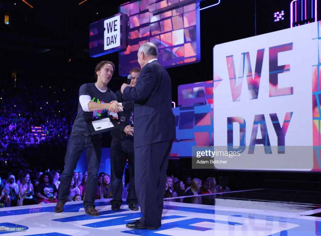 Craig Kielburger shakes the hand of Minnesota Governor Mark Dayton while Marc Kielburger watches during the We Day Minnesota event at the Xcel Energy Center in St. Paul, Minnesota on October 8, 2013