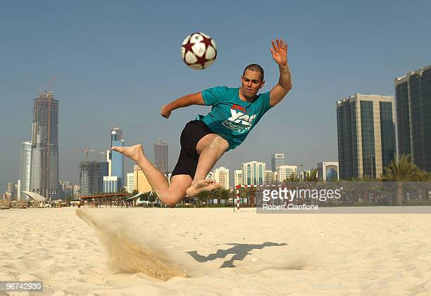 Craig Lowndes driver of the Team Vodafone Holden kicks a ball on the beach after a game of beach soccer during previews for round one of the V8...