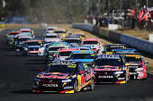 Craig Lowndes drives the Red Bull Racing Australia Holden leads Jamie Whincup drives the Red Bull Racing Australia Holden at the start of race 23 for...