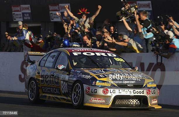 Craig Lowndes of Team Betta Electrical drives past his pit crew after crossing the line to win the V8 Supercars Bathurst 1000 at the Mount Panorama...