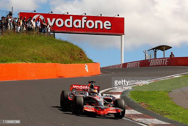 Craig Lowndes of Team Vodafone Holden Team drives the Vodafone McLaren Mercedes of Jenson Button of Great Britain at Mount Panorama on March 22 2011...