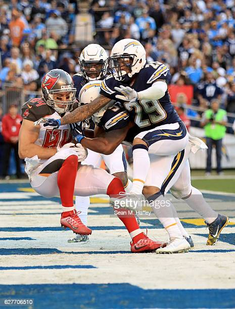 Craig Mager and Jatavis Brown of the San Diego Chargers tackle Cameron Brate of the Tampa Bay Buccaneers as he scores a touchdown on a short pass...