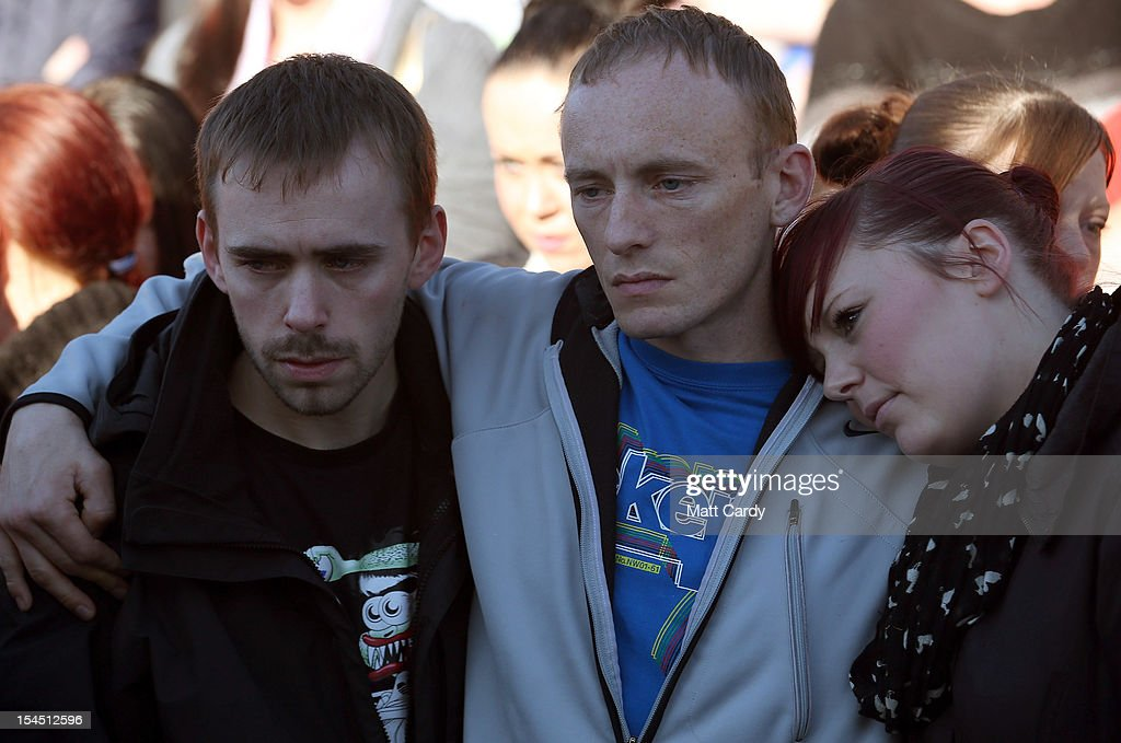 Craig Menzies, (C) comforts his brother Gareth Menzies (L) and sister Laura Williams as they attend a local community memorial vigil outside Ely Fire Station for their 32-year-old sister, Karina Menzies, who was killed in a hit-and-run collision on October 21, 2012 in Cardiff, Wales. Detectives are questioning a 31-year-old man arrested on suspicion of murder after a series of hit-and-runs in Cardiff that left a woman dead and 13 people injured. Nine casualties, five of them children, are still in hospital. Two adults are in critical but stable conditions.