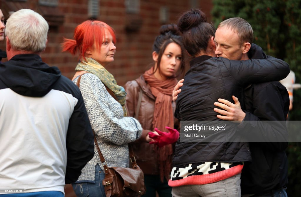 Craig Menzies, whose sister Karina Menzies was killed on Friday, is comforted as he leaves a special service of prayer and reflection held for those affected by the hit-and-run incidents in Cardiff at the Church of the Resurrection on Grand Avenue on October 21, 2012 in Cardiff, Wales. Detectives are questioning a 31-year-old man arrested on suspicion of murder after a series of hit-and-runs in Cardiff that left a woman dead and 13 people injured. Nine casualties, five of them children, are still in hospital. Two adults are in critical but stable conditions.
