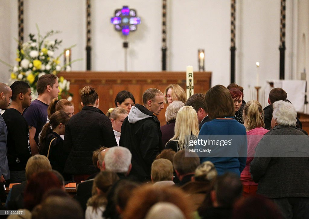Craig Menzies (centre in grey hoodie), whose sister Karina Menzies was killed on Friday, stands to light a candle as people gather for a special service of prayer and reflection held for those affected by the hit-and-run incidents in Cardiff at the Church of the Resurrection on Grand Avenue on October 21, 2012 in Cardiff, Wales. Detectives are questioning a 31-year-old man arrested on suspicion of murder after a series of hit-and-runs in Cardiff that left a woman dead and 13 people injured. Nine casualties, five of them children, are still in hospital. Two adults are in critical but stable conditions.