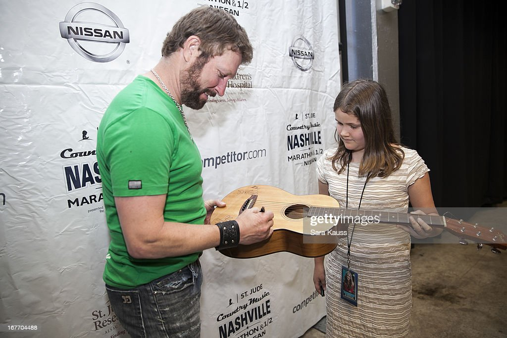 Craig Morgan (L) signs an autograph on a guitar for a fan as he attends the St Jude Country Music Marathon and Half Marathon Post Race Concert presented by Nissan on April 27, 2013 in Nashville, Tennessee.