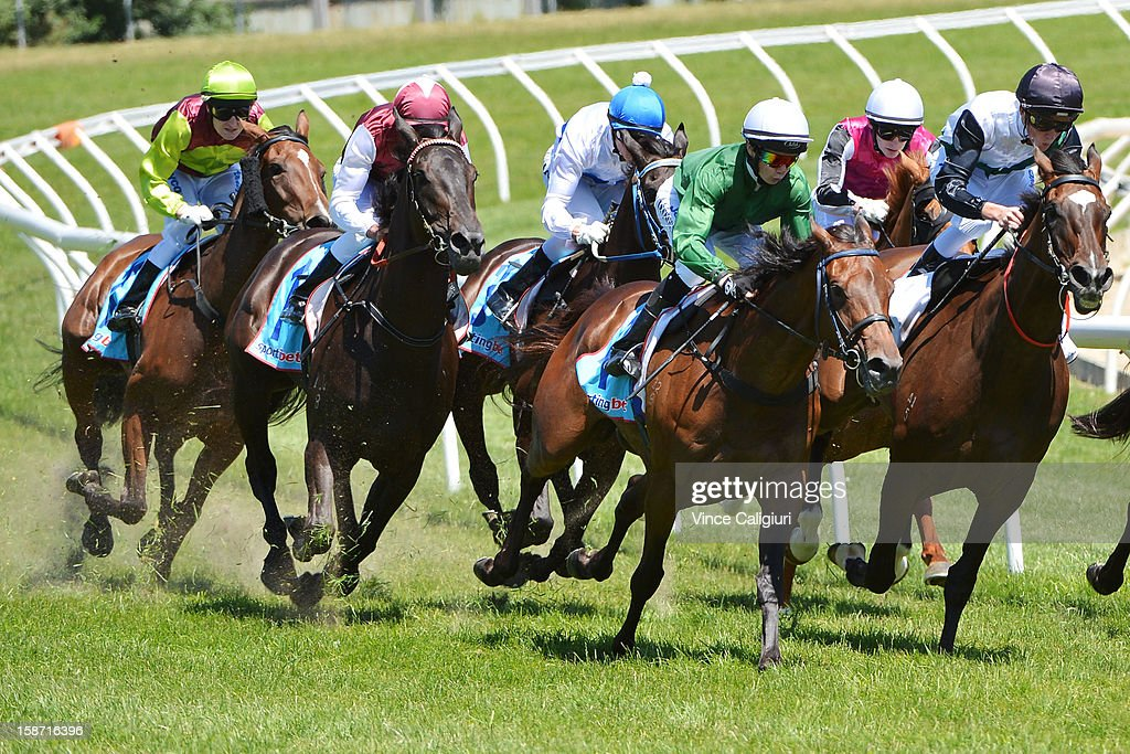 Craig Newitt riding Bells of Troy (L) is last on the home turn before going on to win the Frank O'Brien Handicap at Caulfield Racecourse on December 26, 2012 in Melbourne, Australia.