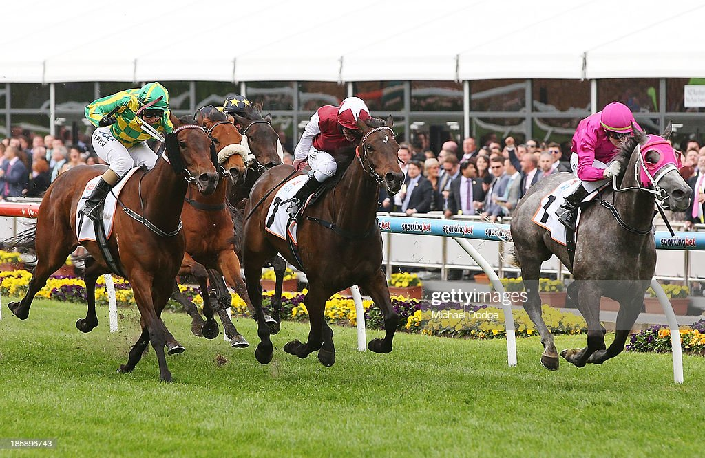 Craig Newitt (R) riding Catkins defeats Michelle Payne (L) riding Lake Sententia and Kerrin McEvoy (C) riding Cameo to win race 9 the Eliza Park International Stakes during Cox Plate Day at Moonee Valley Racecourse on October 26, 2013 in Melbourne, Australia.