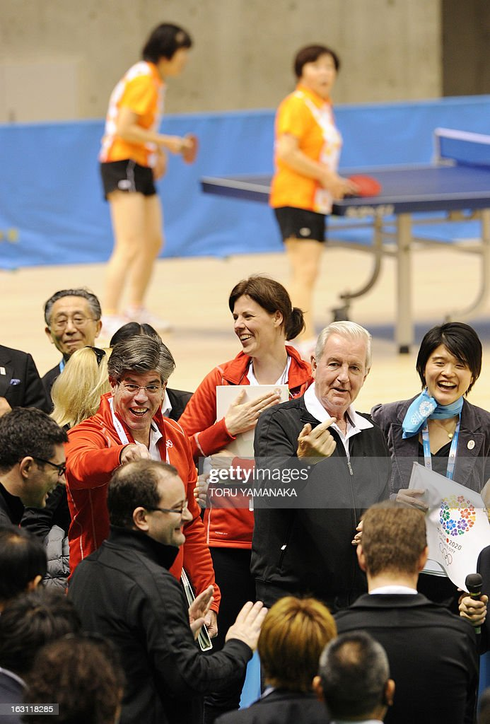 Craig Reedie (centre R), chair of the International Olympic Committee (IOC) evaluation commission gestures to IOC member Patrick Baumann (front L) of Switzerland to play table tennis with Japan's Olympian Ai Fukuhara during the inspector's visit to Tokyo Metropolitan Gymnasium, the potential location for the 2020 Olympic Games table tennis, in Tokyo on March 5, 2013. Japan's corporate giants are ready to chip in for another Summer Olympics in Tokyo, hoping the Games will provide the same economic boost as the 1964 edition, Toyota's chairman said on march 5. AFP PHOTO / Toru YAMANAKA