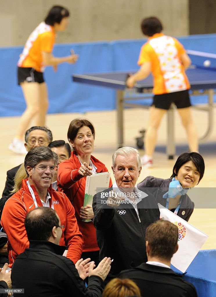 Craig Reedie (C), chair of the International Olympic Committee (IOC) evaluation commission, gestures to IOC member Patrick Baumann (front L) of Switzerland to play table tennis with Japan's Olympian Ai Fukuhara during the inspector's visit to Tokyo Metropolitan Gymnasium, the potential location for the 2020 Olympic Games table tennis, in Tokyo on March 5, 2013. Japan's corporate giants are ready to chip in for another Summer Olympics in Tokyo, hoping the Games will provide the same economic boost as the 1964 edition, Toyota's chairman said on march 5. AFP PHOTO / Toru YAMANAKA
