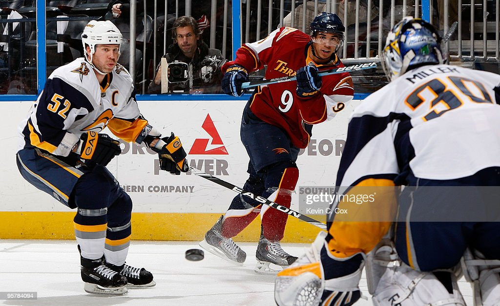 Craig Rivet of the Buffalo Sabres defends as Evander Kane of the Atlanta Thrashers shoots against goaltender Ryan Miller at Philips Arena on January...