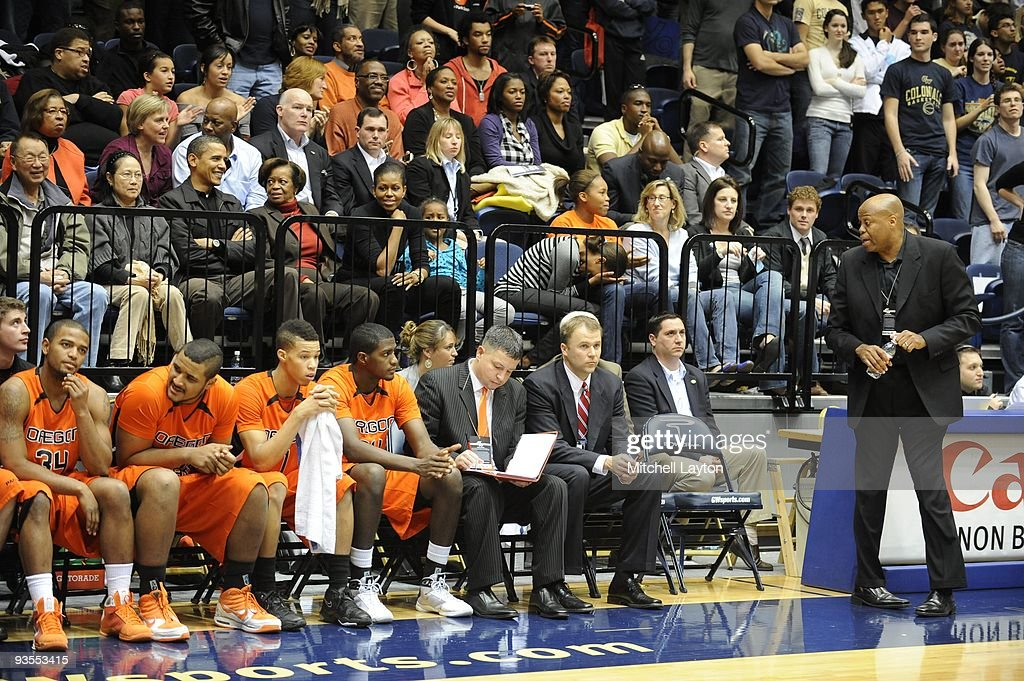Craig Robinson head coach of the Oregon State Beavers with President Barack Obama behind him during a college basketball game against the George...