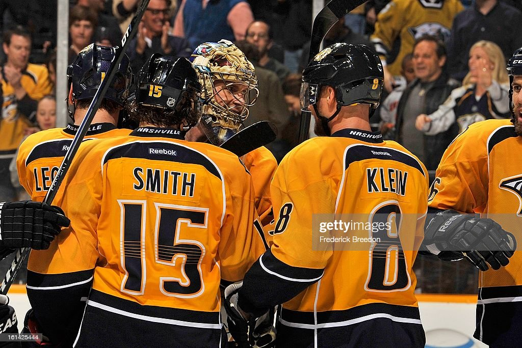 Craig Smith #15 and Kevin Klein #8 of the Nashville Predators congratulate teammate goalie Pekka Rinne #35 on defeating the Los Angeles Kings at the Bridgestone Arena on February 7, 2013 in Nashville, Tennessee.