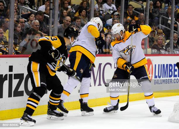 Craig Smith and Nick Bonino of the Nashville Predators fight for the puck along the boards against Olli Maatta of the Pittsburgh Penguins at PPG...
