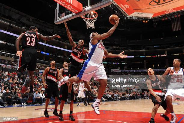 Craig Smith of the Los Angeles Clippers goes up for a reverse layup against Martell Webster and Dante Cunningham of the Portland Trail Blazers at...