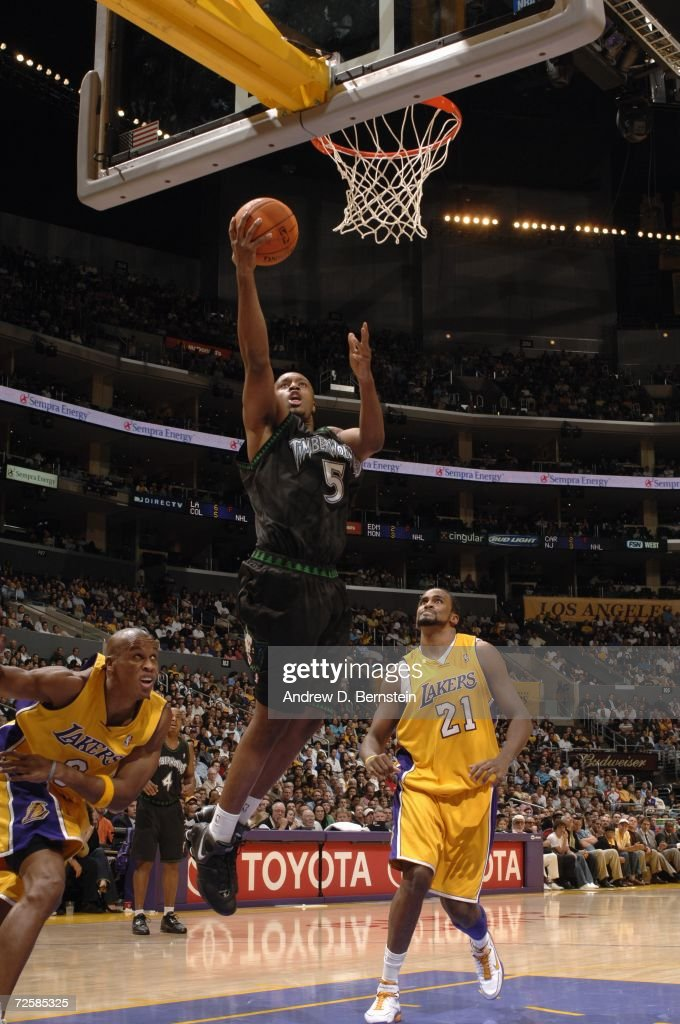 Craig Smith of the Minnesota Timberwolves drives to the basket for a layup past Maurice Evans and Ronny Turiaf of the Los Angeles Lakers during the...