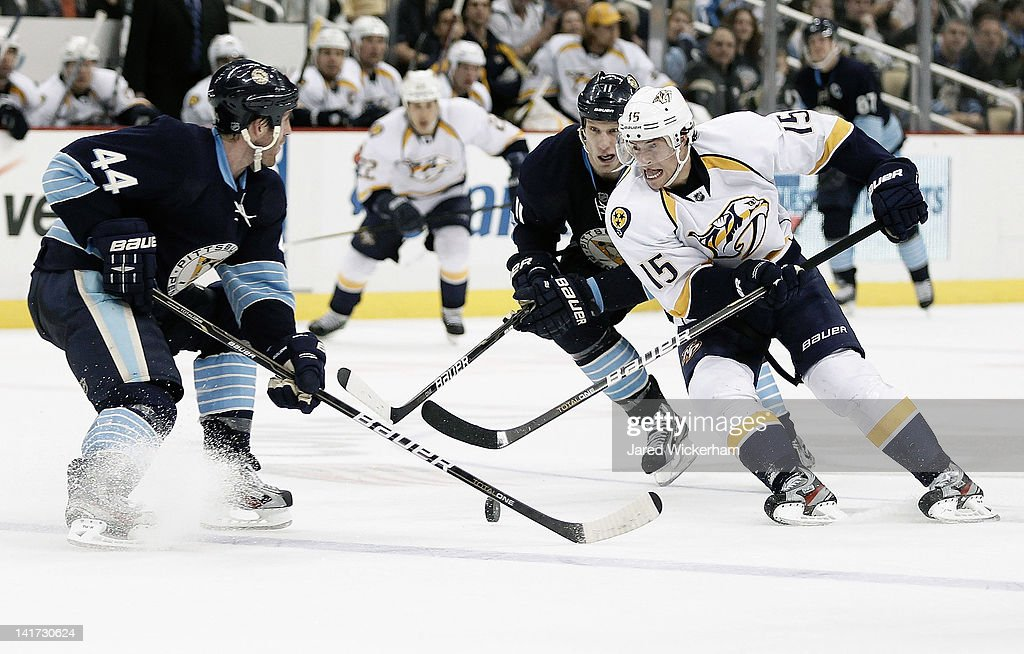 Craig Smith #15 of the Nashville Predators attempts to carry the puck between Brooks Orpik #44 and Jordan Staal #11 of the Pittsburgh Penguins during the game on March 22, 2012 at CONSOL Energy Center in Pittsburgh, Pennsylvania.