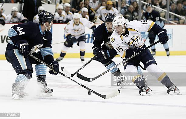 Craig Smith of the Nashville Predators attempts to carry the puck between Brooks Orpik and Jordan Staal of the Pittsburgh Penguins during the game on...
