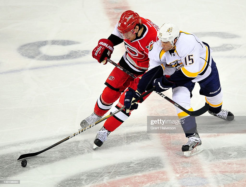 Craig Smith #15 of the Nashville Predators battles for the puck with Andreas Nodl #14 of the Carolina Hurricanes during play at the RBC Center on February 28, 2012 in Raleigh, North Carolina. The Hurricanes won 4-3.