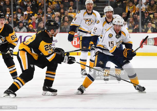 Craig Smith of the Nashville Predators eyes the puck against Ian Cole of the Pittsburgh Penguins at PPG Paints Arena on January 31 2017 in Pittsburgh...