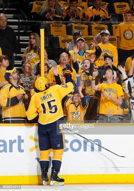 Craig Smith of the Nashville Predators tosses a puck to fans during warmups against the Philadelphia Flyers prior to an NHL game at Bridgestone Arena...