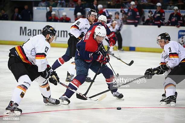 Craig Smith of USA is challenged by Tobias Rieder and Justin Krueger of Germany during the international ice hockey friendly match between Germany...