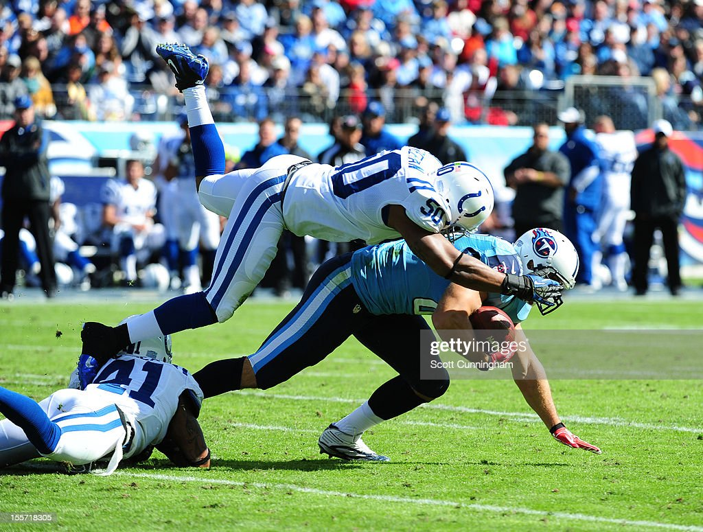 Craig Stevens #88 of the Tennessee Titans is tackled by Jerrell Freeman #50 and Antoine Bethea #41 of the Indianapolis Colts at LP Field on October 28, 2012 in Nashville, Tennessee.