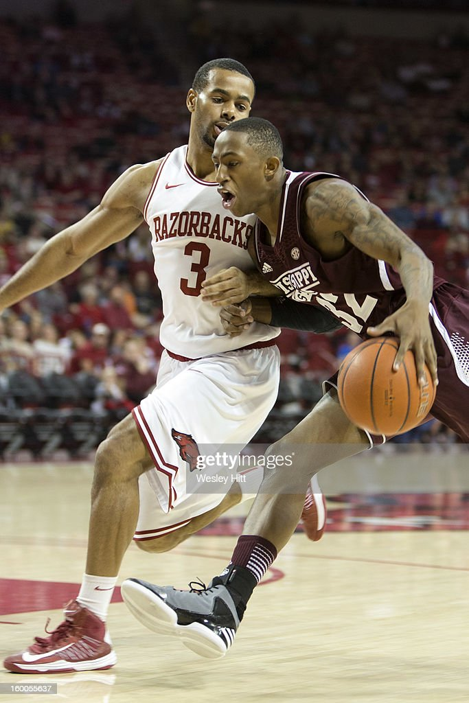 Craig Sword #32 of the Mississippi State Bulldogs drives to the basket against Rickey Scott #3 of the Arkansas Razorbacks at Bud Walton Arena on January 23, 2013 in Fayetteville, Arkansas. The Razorbacks defeated the Bulldogs 96-70.