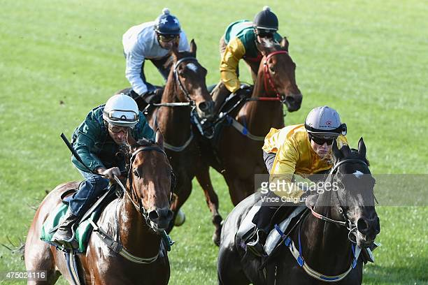 Craig Williams riding Brazen Beau defeats Damien Oliver riding Wandjina in a jump out down the straight course at Flemington Racecourse on May 29...