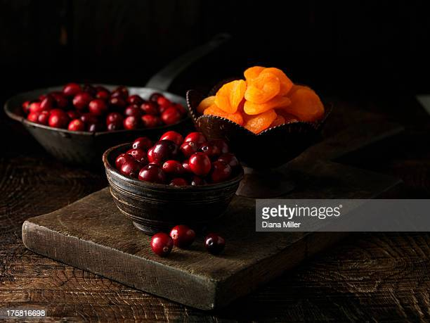 Cranberries and dried apricots on dark wooden board
