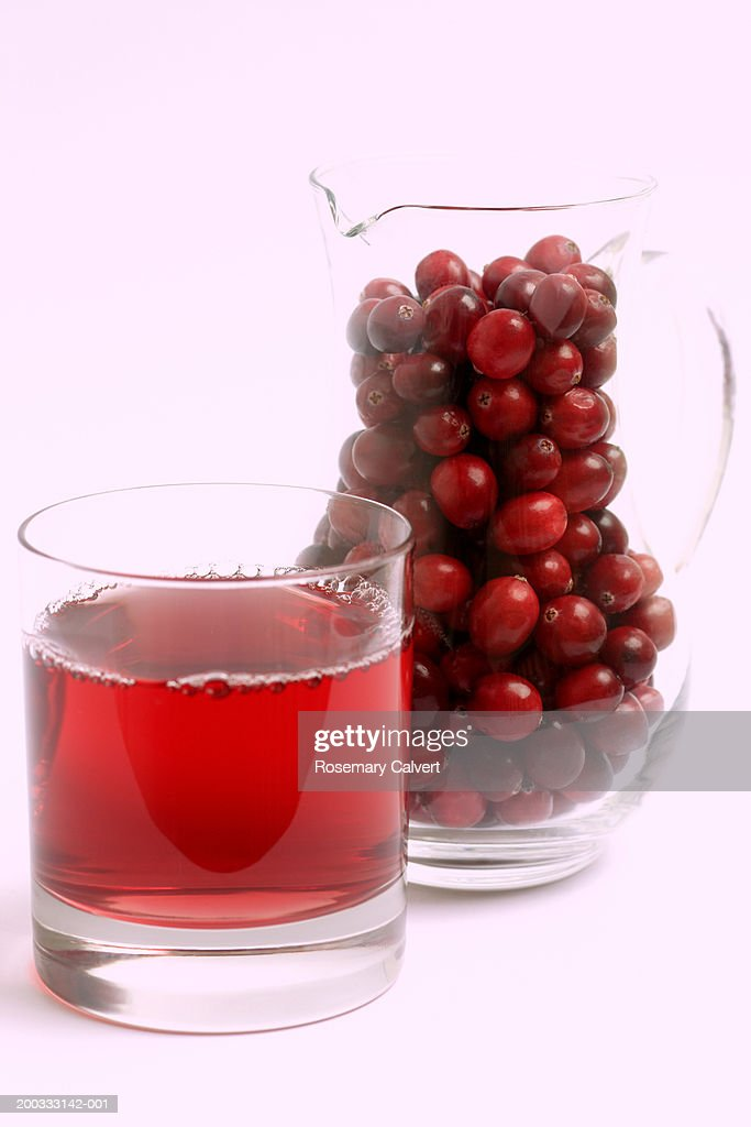 Cranberries by glass of cranberry juice, close-up