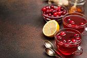 cranberries lemon ginger drink in a glass cup, honey, half a lemon, slices of ginger on a dark background